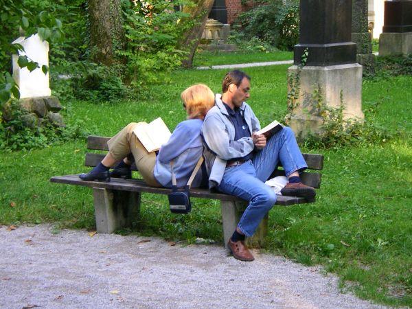 Lesendes Paar auf Parkbank